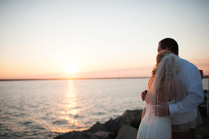 romantic bridal couple watching the sunset from Oceanside Marina Suites