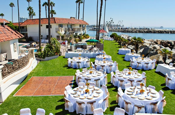Wedding reception table decorated and set with palm trees and the ocean in the back