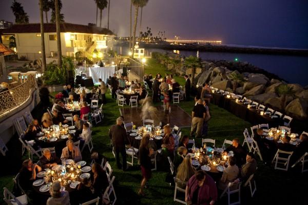 Outdoor wedding reception at night with table light decorations and the ocean